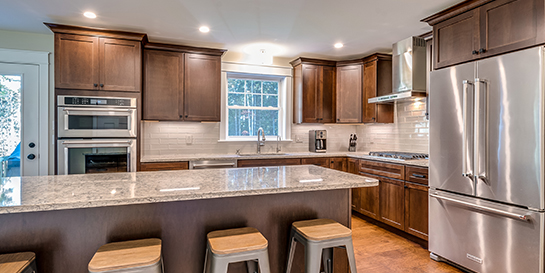 quartz countertop kitchen dark wood cabinets wide plank hardwood flooring