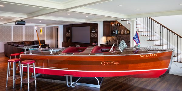 custom designed antique wood boat bar with red bar stools in basement entertainment space